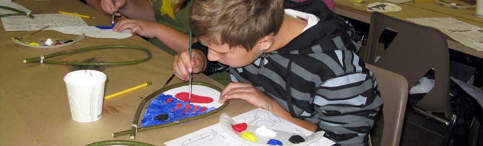 Young boy painting a Mandala