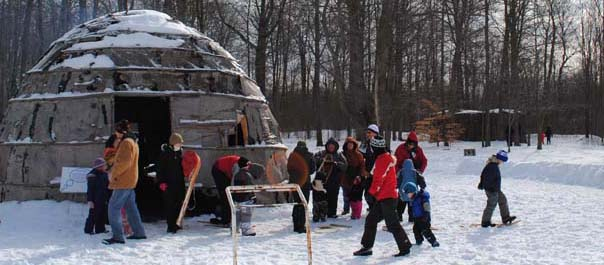 Children and adults enjoying Winter Festival activities in front of the Longhouse