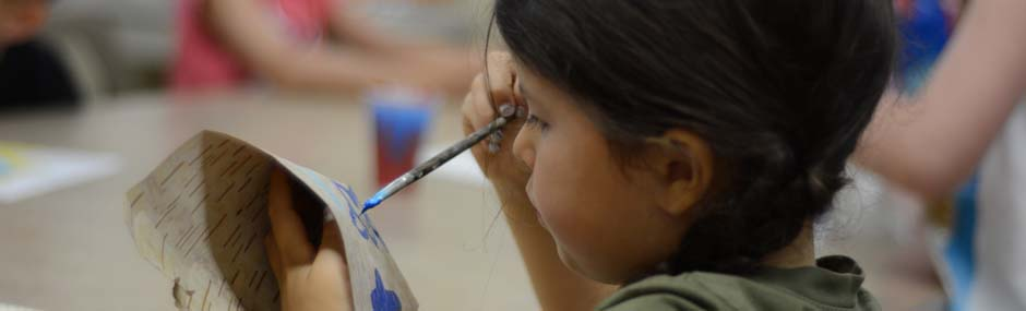 Young girl painting Birch bark at a workshop