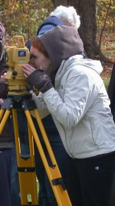 Picture of student using a transit to map the Lawson Site