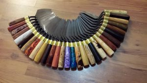Image of trowels arranged in a crescent shape with multiple coloured handles made of wood