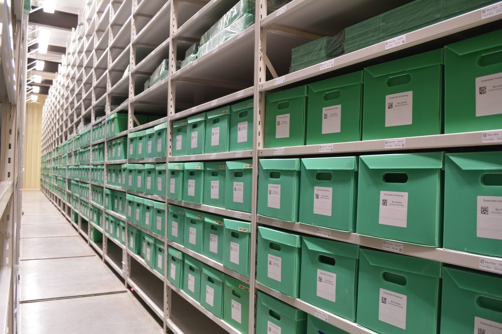 Long rows of labelled green boxes sitting neatly on metal shelving in the Museum of Ontario Archaeology's  collections repository.